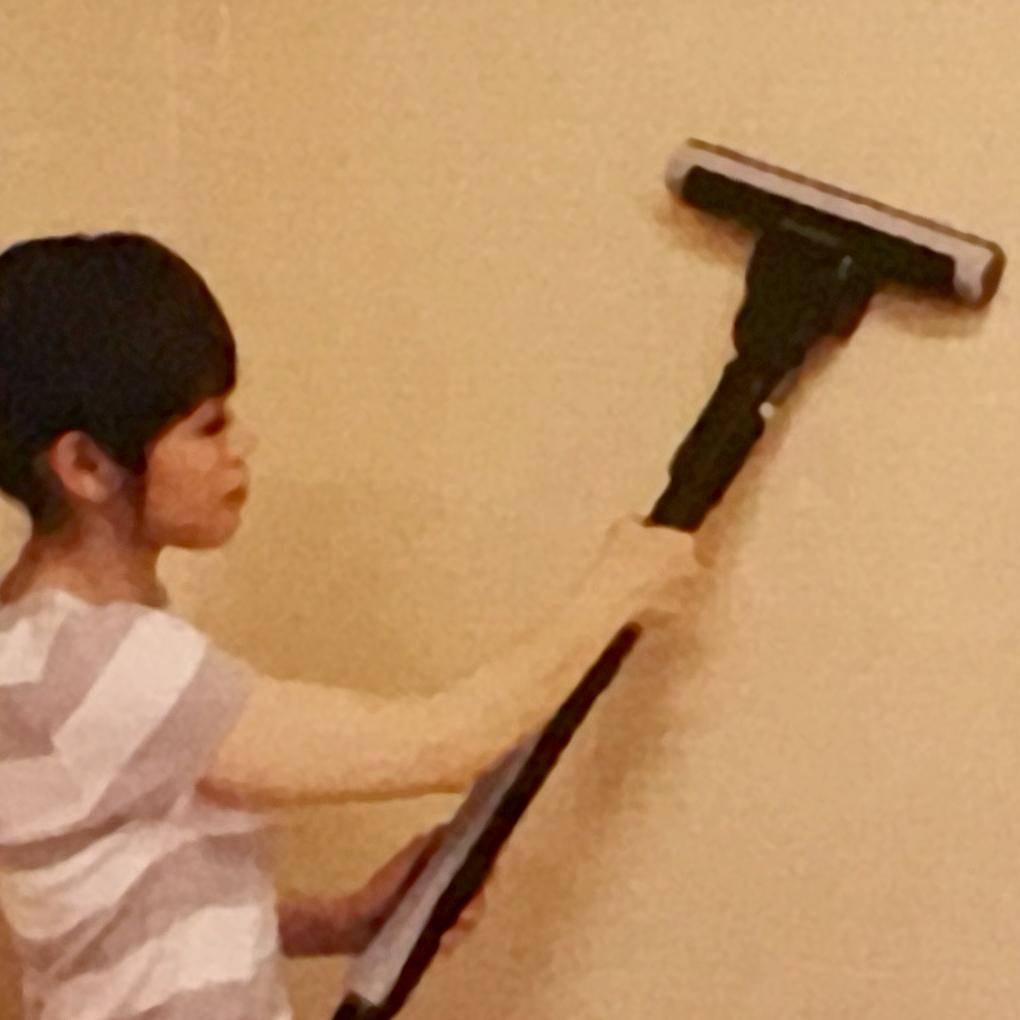 壁の表面を掃除機で吸う